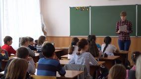 Mujer joven del profesor delante de la clase en la pizarra metrajes