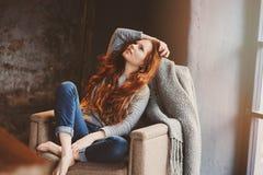 Mujer joven del readhead que se relaja en casa en la silla acogedora, vestida en suéter casual y vaqueros Fotos de archivo