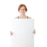 Mujer joven del redhead con la tarjeta en blanco Imagenes de archivo