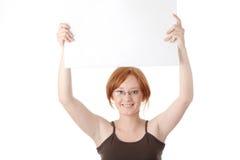 Mujer joven del redhead con la tarjeta en blanco Imágenes de archivo libres de regalías