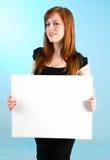 Mujer joven del Redhead que lleva a cabo una muestra blanca en blanco Imágenes de archivo libres de regalías