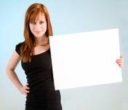 Mujer joven del Redhead que lleva a cabo una muestra blanca en blanco Imagen de archivo