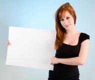 Mujer joven del Redhead que lleva a cabo una muestra blanca en blanco Fotos de archivo libres de regalías