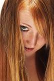 Mujer joven del redhead que mira a través de su pelo Fotografía de archivo