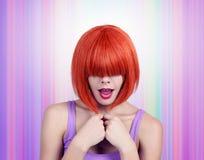 Mujer joven del retrato con el pelo rojo y la explosión que la cubren ojos fotografía de archivo libre de regalías