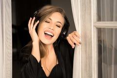Mujer joven del retrato con los auriculares que canta y que escucha la música en casa Ella lleva en seda negra del ANG de la ropa Fotos de archivo