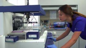 Mujer joven del retrato en uniforme azul y los guantes de goma que controlan la fabricación en el laboratorio, prueba de la droga metrajes