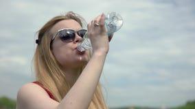 Mujer joven del retrato que bebe la agua fría de una botella plástica en día de verano caliente almacen de metraje de vídeo