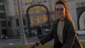 Mujer joven del retrato que monta una bicicleta en ciudad de la tarde y que mira en cámara metrajes