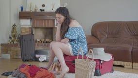 Mujer joven del retrato que se sienta en la maleta y el pensamiento almacen de video