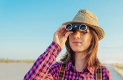 Mujer joven del viajero que mira a través de los prismáticos fotos de archivo libres de regalías