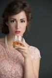 Mujer joven del vintage que lleva a cabo una bebida Foto de archivo