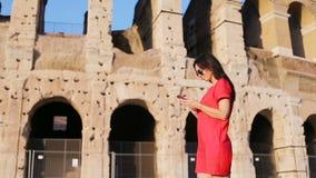Mujer joven delante de Colosseum con el teléfono elegante en manos en Roma, Italia Muchacha en las vacaciones de Europa almacen de video