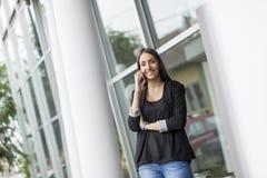 Mujer joven delante de la oficina Fotos de archivo