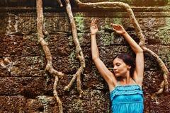 Mujer joven delante de la pared del templo de Angkor Imágenes de archivo libres de regalías
