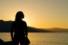 Mujer joven delante de la puesta del sol Fotos de archivo libres de regalías