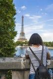 Mujer joven delante de la torre Eiffel Imagenes de archivo