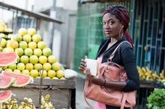 Mujer joven delante de un estante de la fruta Foto de archivo