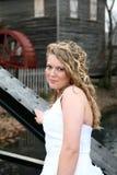 Mujer joven delante de un molino del grano para moler Fotografía de archivo libre de regalías