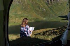 Mujer joven delante de una tienda en las montañas suizas que lee un libro imágenes de archivo libres de regalías