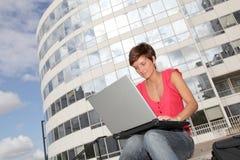 Mujer joven delante del edificio de la universidad Fotografía de archivo