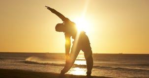 Mujer joven delgada atlética que ejercita y que estira al aire libre en parque metrajes