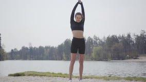 Mujer joven delgada encantadora que hace los ejercicios del deporte, colocándose en el riverbank Paisaje hermoso en el fondo metrajes
