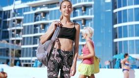 Mujer joven delgada hermosa en ropa de deportes y con la pequeña mochila que camina en la costa contra hotel grande Hembra feliz almacen de metraje de vídeo