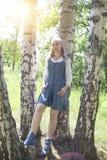 Mujer joven delgada hermosa en sundress azules y una blusa blanca cerca de un abedul en día soleado Foto de archivo libre de regalías