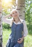 Mujer joven delgada hermosa en sundress azules y una blusa blanca cerca de un abedul en día soleado Imagenes de archivo