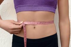 Mujer joven delgada que mide su cintura fotografía de archivo