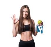 Mujer joven delgada y sana que sostiene la cinta de la medida y manzana aislada en el fondo blanco Pérdida de peso y concepto de  Fotos de archivo libres de regalías