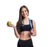 Mujer joven delgada y sana que sostiene la cinta de la medida y manzana aislada en el fondo blanco Pérdida de peso y concepto de  imagenes de archivo