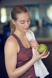 Mujer joven deportiva apta que comtempla una manzana verde fresca imagenes de archivo