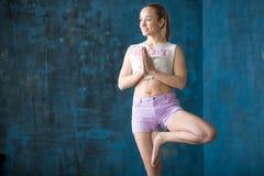 Mujer joven deportiva atractiva que hace la actitud de Vrksasana Fotos de archivo libres de regalías