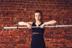 Mujer joven deportiva con el barbell Imágenes de archivo libres de regalías