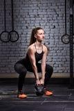 Mujer joven deportiva con el cuerpo muscular que hace entrenamiento del crossfit con el kettlebell contra la pared de ladrillo Imagen de archivo libre de regalías