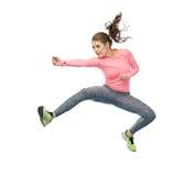Mujer joven deportiva feliz que salta en actitud que lucha Fotografía de archivo libre de regalías