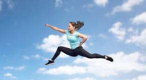 Mujer joven deportiva feliz que salta en actitud que lucha Foto de archivo