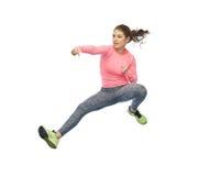 Mujer joven deportiva feliz que salta en actitud que lucha Imagenes de archivo