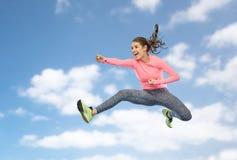 Mujer joven deportiva feliz que salta en actitud que lucha Imagen de archivo