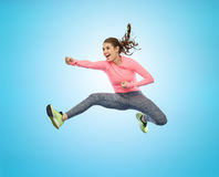 Mujer joven deportiva feliz que salta en actitud que lucha Imágenes de archivo libres de regalías