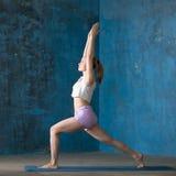 Mujer joven deportiva hermosa que hace alta actitud de la estocada Fotografía de archivo