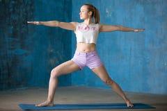 Mujer joven deportiva hermosa que hace postura del guerrero II Fotos de archivo libres de regalías