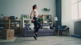 Mujer joven deportiva que corre sobre el terreno en casa practicar disfrutando de actividad metrajes