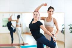 Mujer joven deportiva que hace la actitud Natarajasana de la yoga de rey Dancer con el instructor del instructor en la estera roj imágenes de archivo libres de regalías
