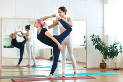 Mujer joven deportiva que hace la actitud Natarajasana de la yoga de rey Dancer con el instructor del instructor en la estera roj fotografía de archivo libre de regalías