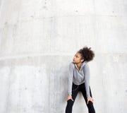 Mujer joven deportiva que se relaja al aire libre con los auriculares Imagen de archivo libre de regalías