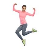 Mujer joven deportiva sonriente feliz que salta en aire Fotos de archivo