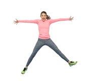 Mujer joven deportiva sonriente feliz que salta en aire Imagen de archivo libre de regalías